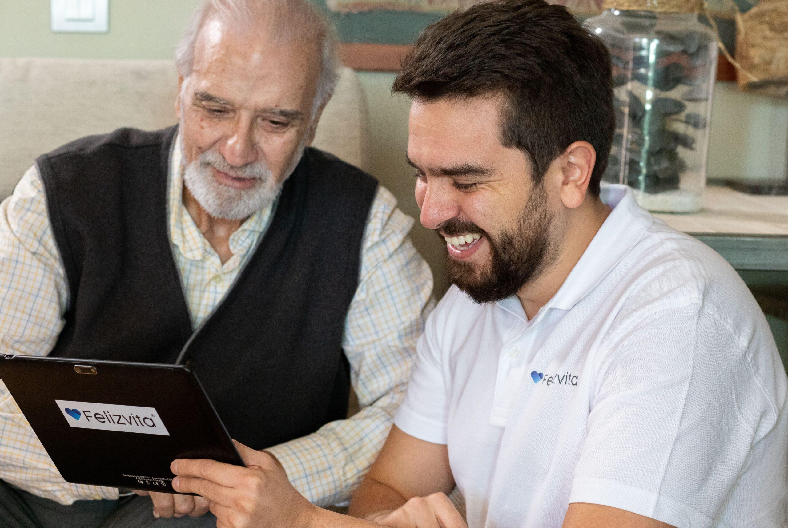 Cuidador de felizvita enseñando teleasistencia a persona mayor