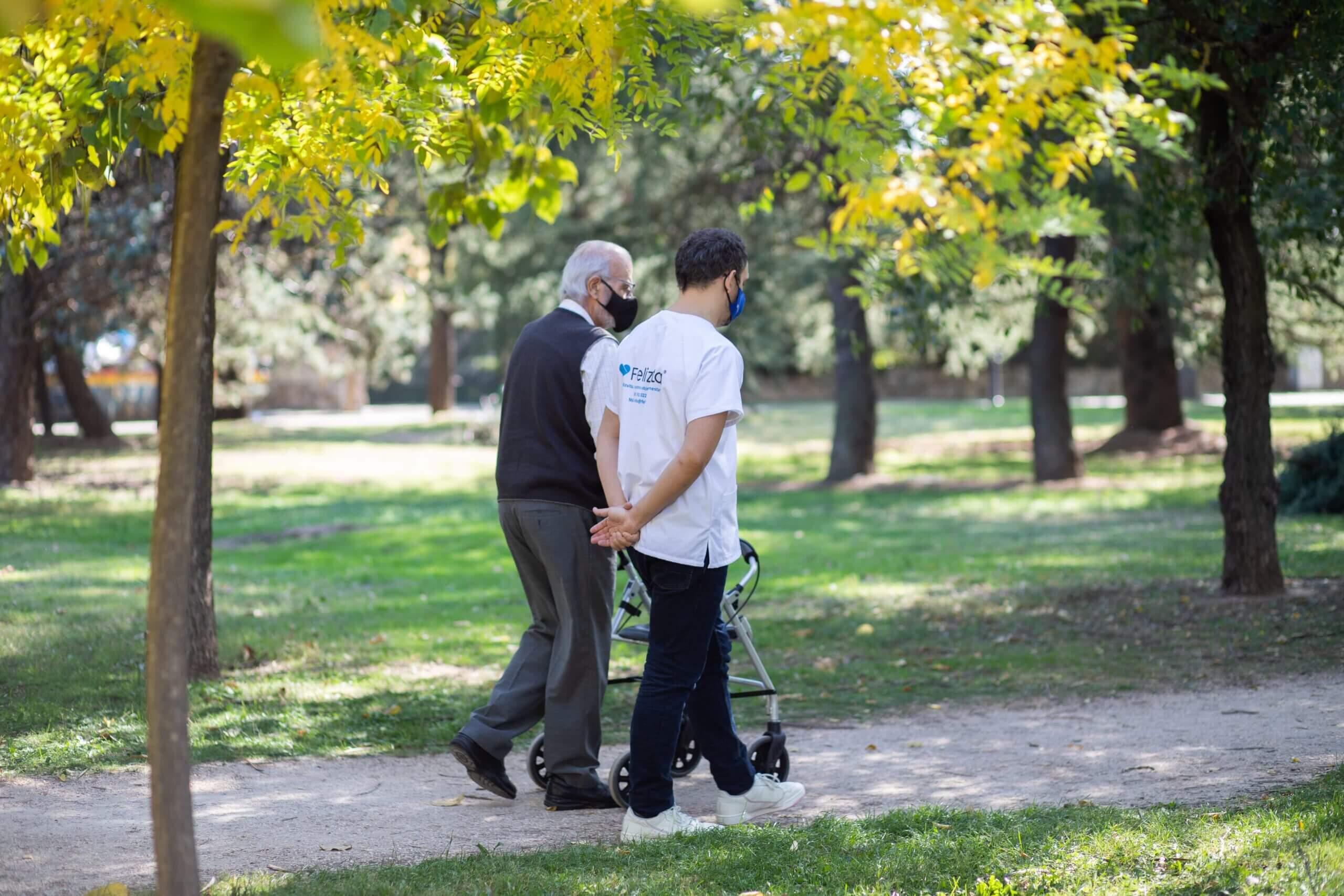 Cuidador a domicilio paseando con persona mayor